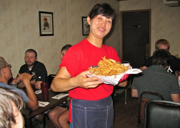 The smiling face of Kitok's, Kyung Brendemuehl, shows off a basket of Kitok's famous oriental fries before serving them to a table of happy patrons.